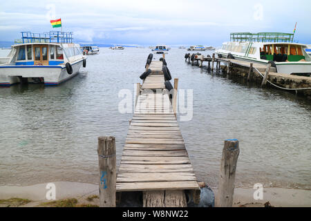 Wooden Docks Surrounded by the Boats to Isla Del Sol on Lake Titicaca at the town of Copacabana, Bolivia, South America - Stock Photo