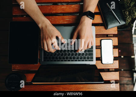 Crop view of male hands using laptop standing on wooden plank table with gadgets and notebook lying around from above - Stock Photo