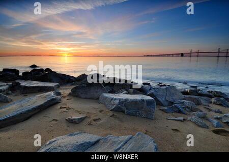 Sunrise on the horizon at the Chesapeake Bay Bridge in Maryland.  Colorful morning skies illuminate foreground rocks along the sandy shoreline. - Stock Photo