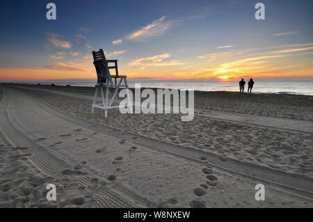 An empty lifeguard chair and a silhouetted couple on an empty beach view scenic skies and a colorful sunrise over the Atlantic Ocean. - Stock Photo