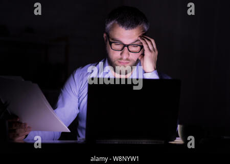 Bearded businessman is doing paper work in front of laptop - Stock Photo