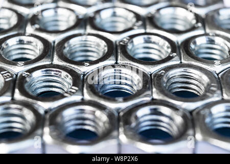 Metal nuts in a row background. Chromed screw nuts isolated. Steel nuts pattern. Set of Nuts and bolts. Tools for work. - Stock Photo