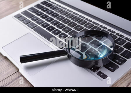 Laptop computer with magnifying glass, concept of search - Stock Photo