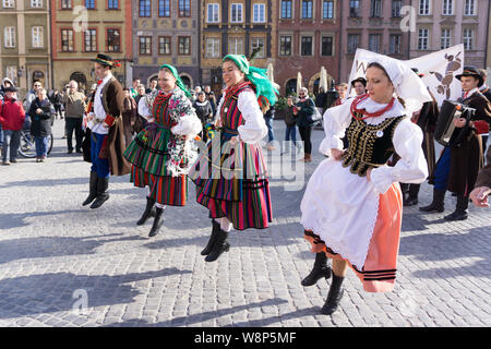 Young people in traditional Lowicz costume are dancing on Warsaw Old Town Square. Dancers dressed in Polish folk costume. - Stock Photo