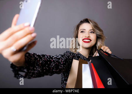 Young smiling woman with bright makeup and curly hair in patterned blouse holding shopping bags and making selfie with mobile phone on gray background - Stock Photo