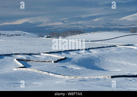 Farmland covered in snow, looking towards the Pennine Fells in Cumbria. - Stock Photo