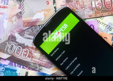 Safaricom M-Pesa fintech microfinance money transaction service on phone with new Kenyan Shilling bank notes background - Stock Photo