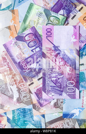 New 2019 Kenyan 100 Shilling bank notes on top of other bank notes in various denominations - Stock Photo