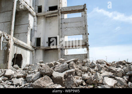 Concrete gray debris close-up on the background of the remains of the destroyed building against the sky. Background - Stock Photo
