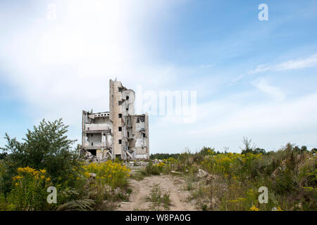 The remains of the structure of a large destroyed building with concrete gray debris around. Background. Text space - Stock Photo