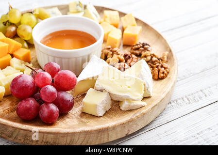 Cheese plate - various types of cheeses with honey, nuts and grapes on a white wooden background closeup - Stock Photo