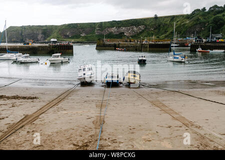 Boats tied up at low tide at Stonehaven Harbour in Aberdeenshire. - Stock Photo