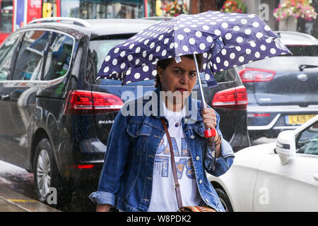 London, UK. 10th Aug, 2019. A woman is seen under an umbrella during a brief rain shower in London. Credit: Steve Taylor/SOPA Images/ZUMA Wire/Alamy Live News - Stock Photo