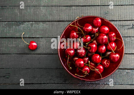 Fresh, ripe cherries in a red glass bowl on black wooden board table background . View from above with copy space