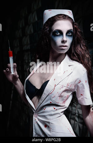 Horror shot: the strange mad nurse (doctor) in bloody uniform, with syringe in hand. Zombie woman (living dead) - Stock Photo