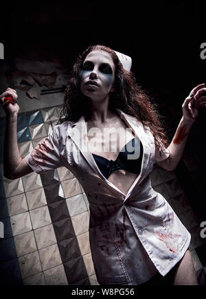 Horror shot: the creepy evil insane nurse (doctor) killing by bloody syringe. Zombie woman (living dead). Monster from nightmare. Grunge texture effec - Stock Photo