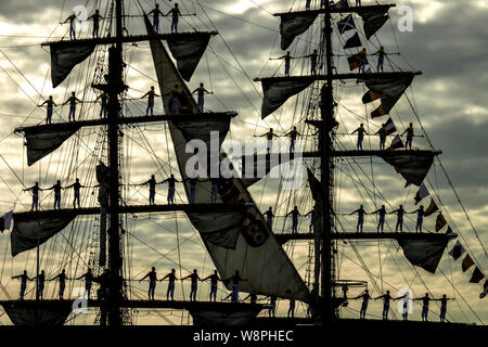 Silhouettes sailors of the Colombian Navy tall ship Gloria standing to attention in salute as the ship arrives for Hanse-sail maritime festival, Rosto - Stock Photo