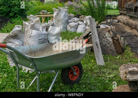 construction waste, transport trolley and other tools are located on the territory of a private garden plot - Stock Photo
