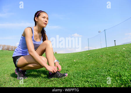 Young sporty woman runner preparing for run in morning in the beautiful nature. Wellness and healthy lifestyle concept with mixed race Asian Caucasian female model going running. - Stock Photo