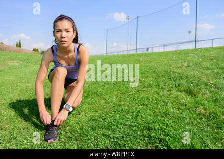 Sporty woman runner preparing for running tying shoe laces in morning on the grass field. Wellness and healthy lifestyle concept with mixed race Asian Caucasian female model going running. - Stock Photo