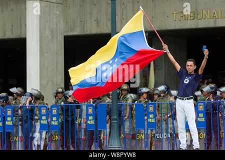 A Venezuelan holds a Venezuelan flag and a Venezuelan Constitution during a protest against Venezuelan President Hugo Chavez