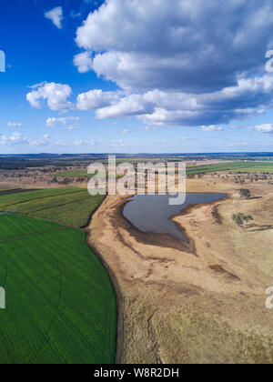 Aerial of lucerne crop grown with a centre pivot irrigation system and nearby water storage showing the surrounding drought affected landscape in cont - Stock Photo