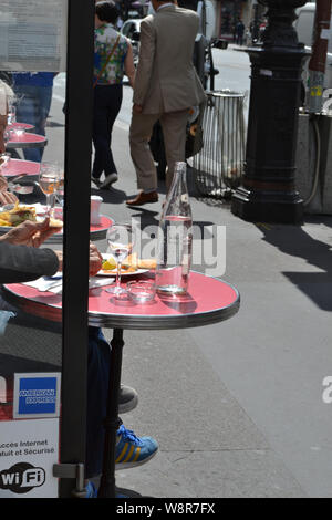 Paris/France - August 19, 2014: Close-up view to tables of a street cafe in Paris in a sunny summer day with tourists eating snack. - Stock Photo