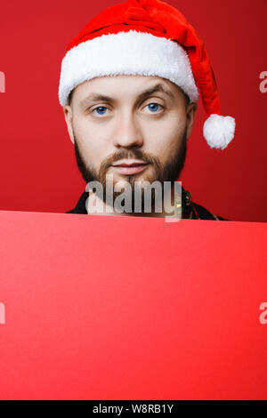 Bearded guy in Christmas hat raising eyebrow and looking at camera while holding empty red poster - Stock Photo