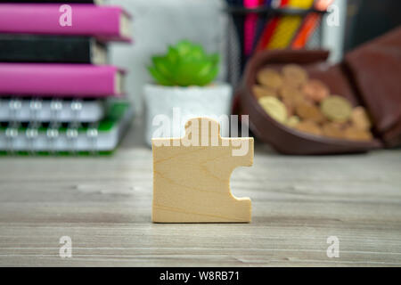 Wooden puzzle piece standing on end on a table with blurred background of books and open purse - Stock Photo