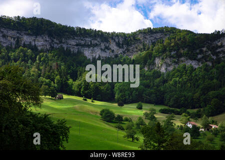 Scenic view on Jura Mountains summer landscape in Switzerland. Green meadow, old barn, coniferous trees at the foot of the rock wall, blue cloud sky. - Stock Photo
