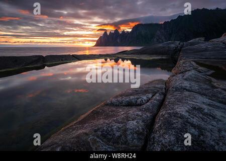 Reflection in a rockpool of impressive Oksen Mountain range at very colorful sunset, Tungeneset, Senja, Norway