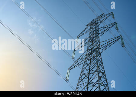 Overhead electrical power lines on a transmission tower against blue sky background. Electric energy distribution concept. Stock Photo