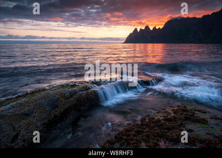 Waves crushing over mighty rocks with impressive oksen Mountains in background at a colorful midnight sunset, Tungeneset, Devils Jaw, Senja, Norw