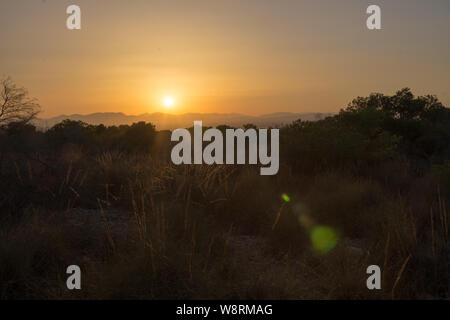 a sunset behind the mountains during a warm Summer evening in August seen over Alicante City - Stock Photo