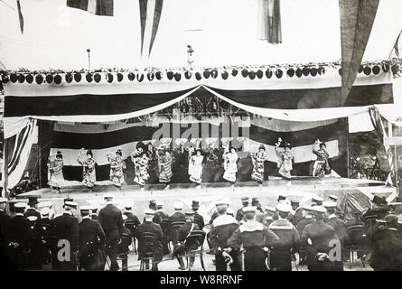 [ 1900s Japan - American White Fleet in Japan ] —   Admiral Sperry and sailors from his crew watch a geisha performance at Yokohama, Kanagawa Prefecture during the visit of the American Great White Fleet in October 1908.   Between December 16, 1907 and February 22, 1909, the fleet called on 20 ports on six continents. As the ships' hulls were painted white, it was popularly known as the Great White Fleet. The fleet's mission was to project American military power, especially towards Japan. - Stock Photo