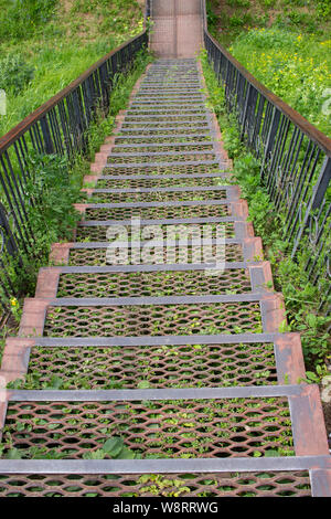 Metal iron staircase leading down. Metal steps iron railings, descending from a green grassy hill. Old rusty iron staircase - Stock Photo
