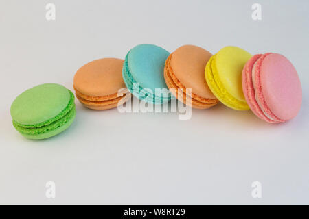 Macaroon sweet biscuits, French pastries of different colors on a white background, macaroni scattered on a white table. Sweet muffins dessert tea dec - Stock Photo