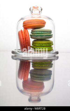 Macaroon cakes in a glass case. Multicolored french sponge cake dessert behind glass, vertical reflection