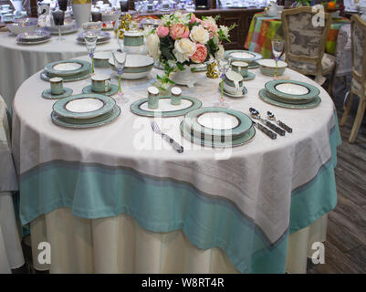 Table setting for 6 persons. Turquoise blue service set on a round table with a tablecloth in color. Festive table, dining table decor - Stock Photo