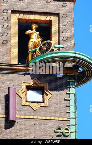COPENHAGEN, DENMARK - JUNE 14, 2019 Copenhagen, Radhuspladsen: the weather girl a golden sculpture torating group telling the weather: the girl with t
