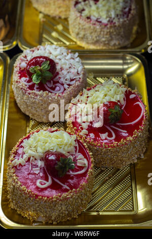 Sponge cake strawberry mini cake with nut crumbs, fresh strawberries in jelly and chocolate chips, round cakes on a coffee shop window - Stock Photo