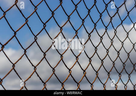 Old rusty mesh netting diagonally against a blue sky with clouds, background wallpaper texture. Rust on a metal fence in a cage