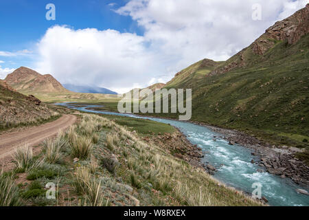 View of the river flowing between green hills with grass and stones in the foreground Kyrgyzstan. Tien Shan - Stock Photo