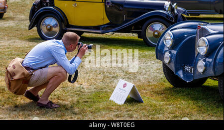 Photographer taking an image of the 1936 Bugatti Type 57S Atlantic in the Cartier Style et Luxe competition. 2019 Foodwood Festival of Speed, Sussex. - Stock Photo
