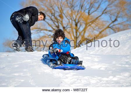 Two Hispanic brothers playing in the snow during a blue sky cold day in the Canadian Winter - Stock Photo