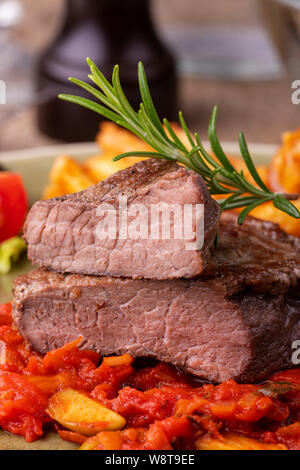 grilled steak on a plate with rosemary - Stock Photo