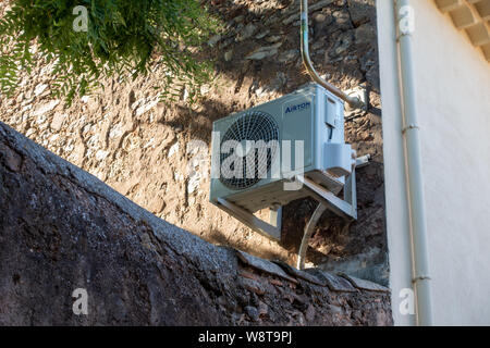Air Conditioning Unit on the outside of house wall - Stock Photo