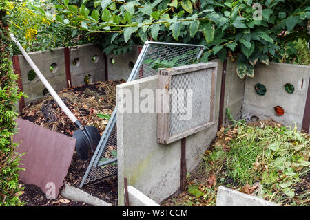 Compost heap in a garden, garden tools for composting - shovel and sieves for sorting the soil - Stock Photo