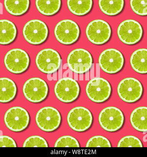 Vibrant fruit pop art background with green lime slices on red background. Minimal flat lay food pattern and texture - Stock Photo