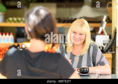 Young depressed woman talking to psychologist during session,mental health.Psychotherapist with patient in cafe. Portrait middle aged woman professional realtor or advisor consulting young happy girl. - Stock Photo